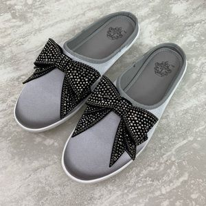 Silver slip on shoes with black jeweled bow.